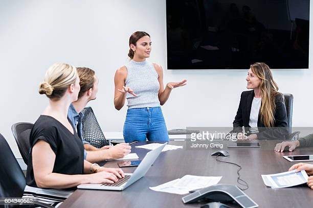 Multi racial group in business meeting, woman explaining