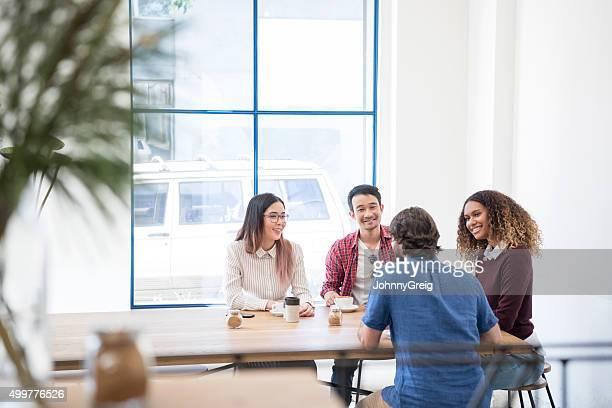 Multi racial group in modern cafe taking coffee break