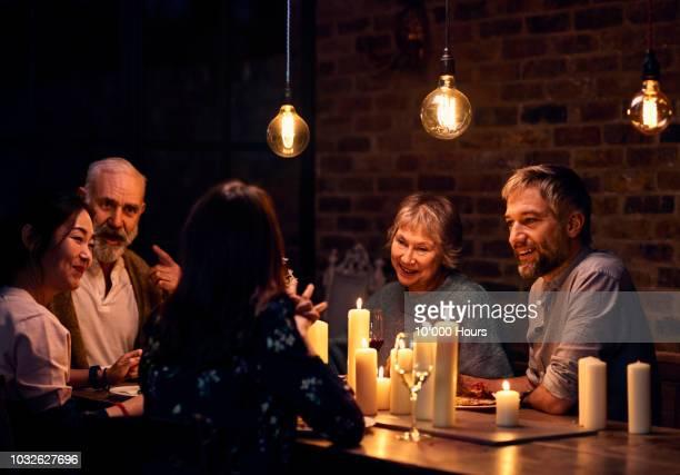 multi racial group of friends in candlelit restaurant having evening meal - invité photos et images de collection