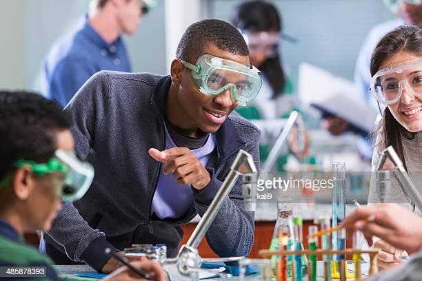 Multi ethniques étudiants en Cours de chimie portant lunettes de sécurité