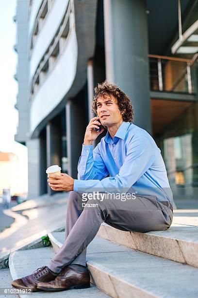 multi tasking businessman using phone during coffee break - drazen stock pictures, royalty-free photos & images