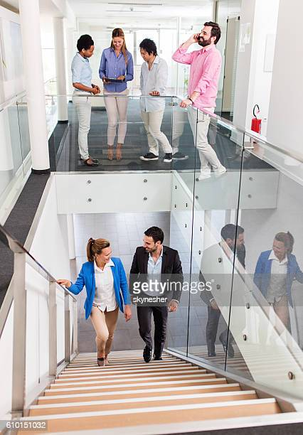 Multi tasking group of business people in a hallway.
