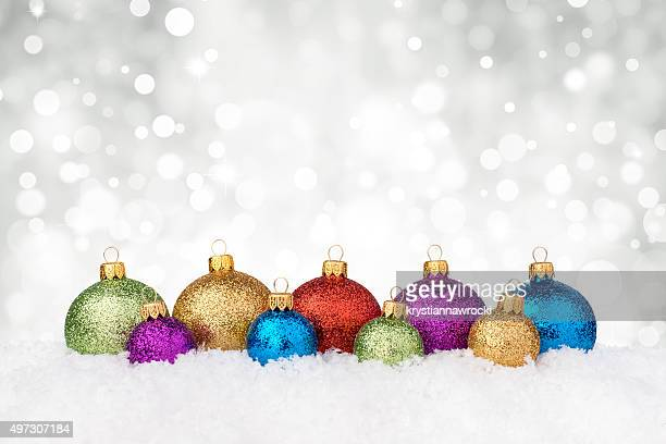 Multicolor different size glitter decorated baubles in a row