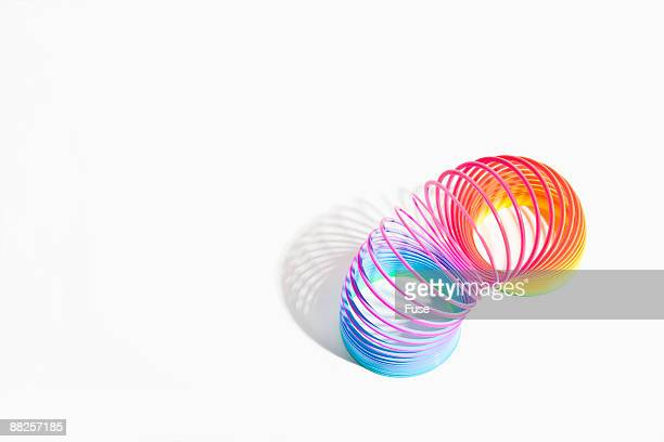 multicolor slinky - metal coil toy stock photos and pictures