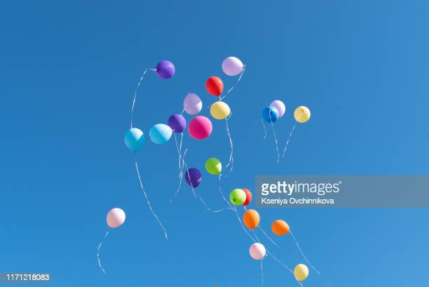 multi-colored balls released into the blue sky. - 風船 ストックフォトと画像