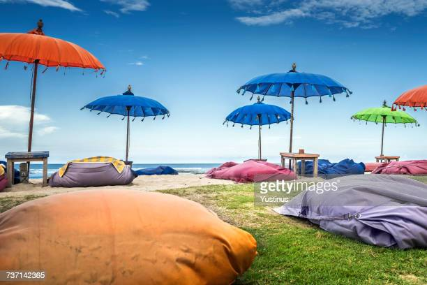 Multi-colored beanbags and parasols on the beach, Bali, Indonesia