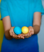 multicolored easter eggs hands