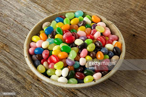Multi-colored jelly beans on rustic wood surface