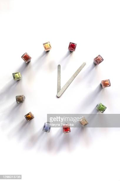 multi-colored nail polishes and nail files in the shape of a clock. - weiblichkeit stock-fotos und bilder