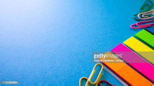 multicolored paper clips and bookmarks on blue background - administrative professional day stock pictures, royalty-free photos & images