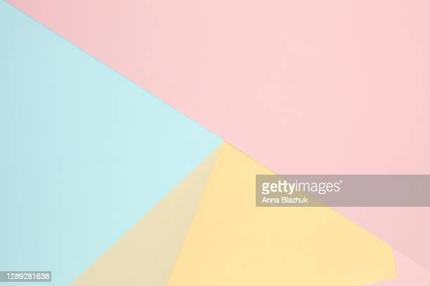 multi-colored paper geometric abstract background of yellow, blue and pink colors. - pastellfarbig stock-fotos und bilder