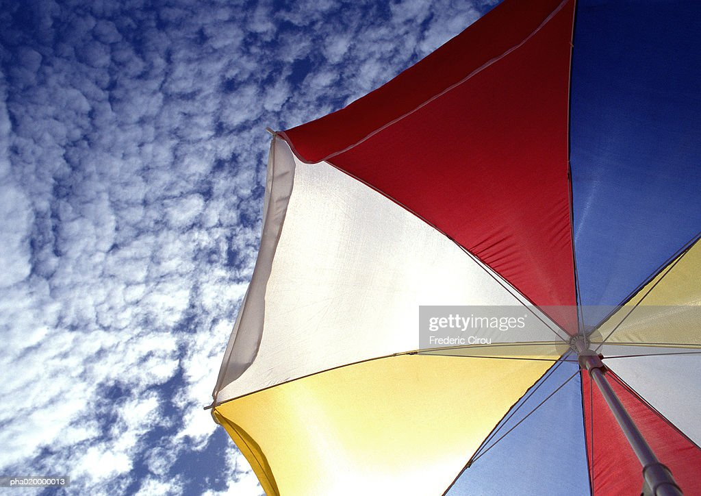 Multi-colored parasol, blue sky with clouds in background, low angle view : Stockfoto