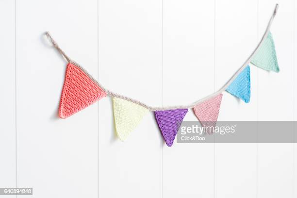 Multicolored pennants hanging on a white wall