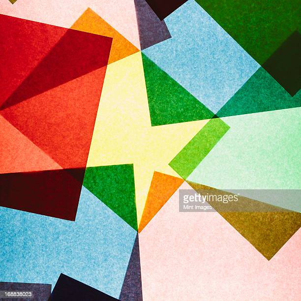 multi-colored pieces of recycled construction paper. shapes, triangles and different colours, above a light source. - triangle percussion instrument stock photos and pictures