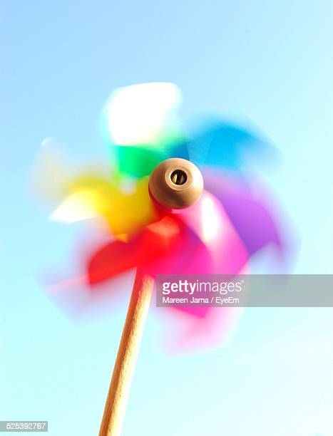 multicolored pinwheel spinning against clear sky - paper windmill stock photos and pictures