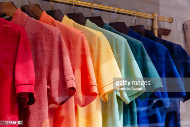 multi-colored polo shirts hanging on a rack in a store - hanging stock pictures, royalty-free photos & images