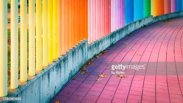 multicolored rainbow fence and purple tiled pathway in autumn - valladolid spanish city stock pictures, royalty-free photos & images
