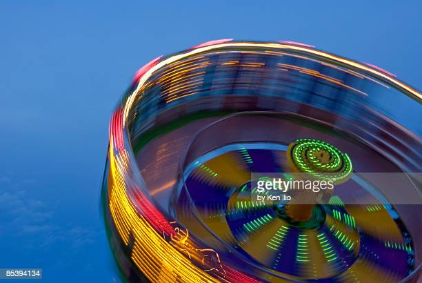 multicolored spinning carnival ride - ken ilio stock photos and pictures