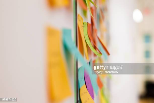 multicolored sticky notes on whiteboard - brainstormen stockfoto's en -beelden