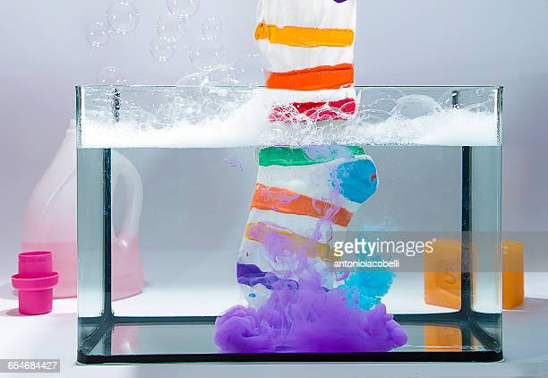 Multi-colored striped stock in tank of water with bleach