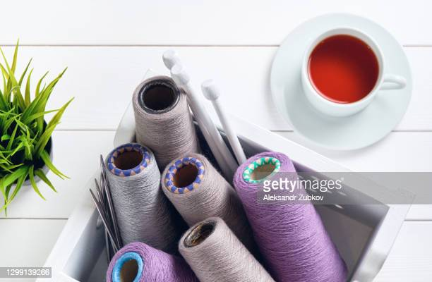 multicolored threads, skeins and balls of italian wool yarn, knitting needles, in a wooden box, on a white background. the concept of knitting, needlework. next to it is a potted flower and a mug of tea. - wool stock pictures, royalty-free photos & images