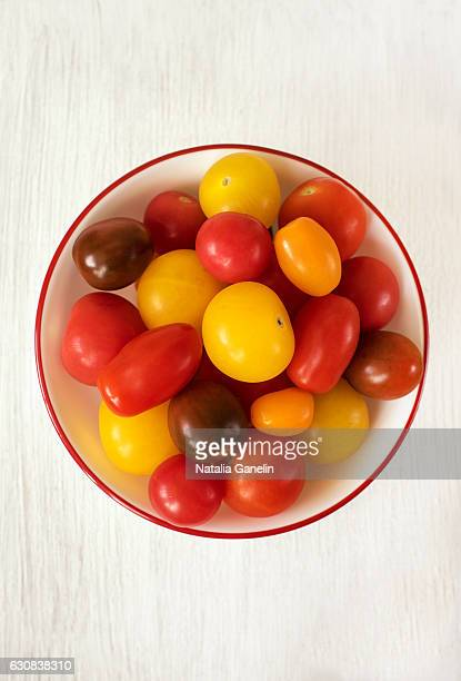 Multicolored tomatoes on white wooden table