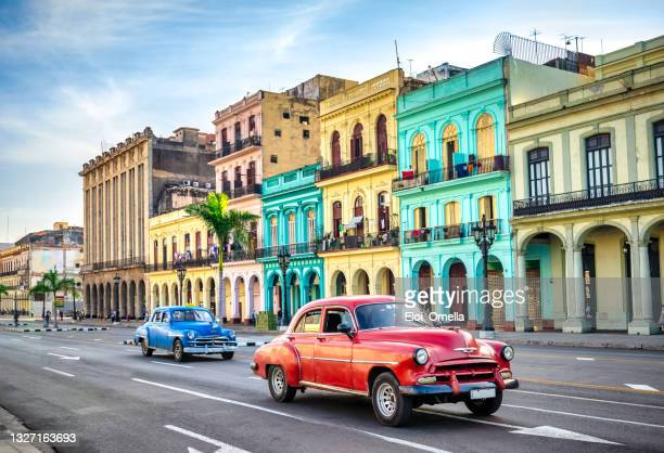 multicolored vintage taxi cars on street of havana against historic buildings - cuba stock pictures, royalty-free photos & images