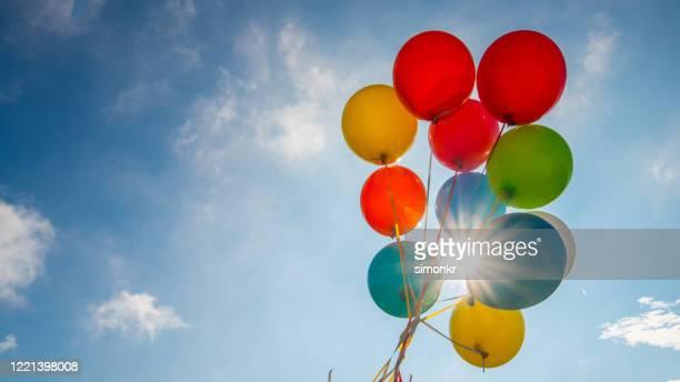 青空に対するマルチカラーの風船 - 風船 ストックフォトと画像