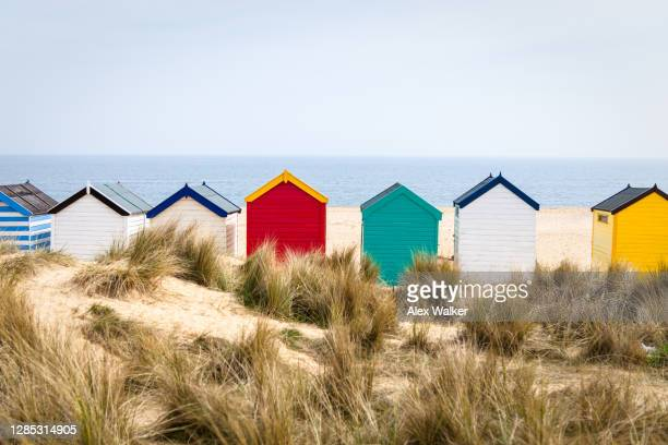 multi-coloured beach huts on sandy beach - coastline stock pictures, royalty-free photos & images