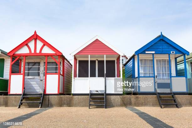 multi-coloured beach huts - front view stock pictures, royalty-free photos & images
