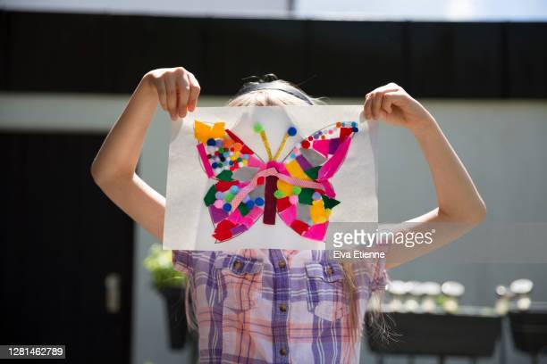 multi-coloured butterfly-shaped art made with felt pieces and pom poms, held up by a child obscuring her face - printed sleeve stock pictures, royalty-free photos & images