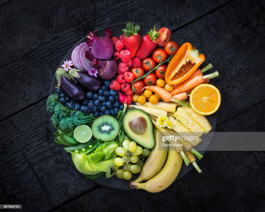 Multicoloured fruit and vegetables in a black bowl on a burnt surface. : Stock Photo