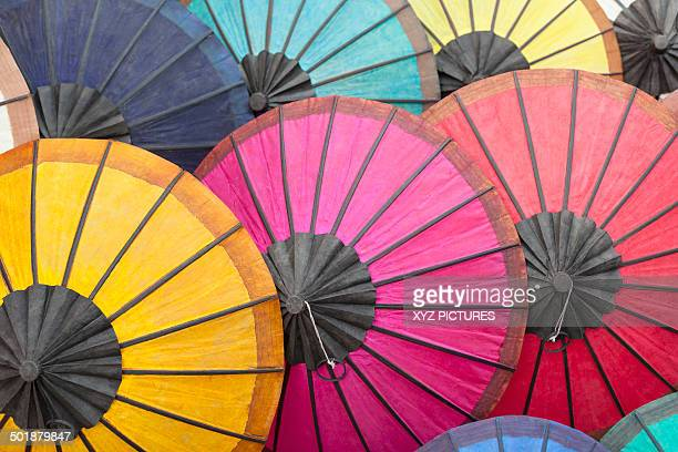 Multicoloured hand-made paper umbrellas or parasols on display at a market in Luang Prabang, Laos, Southeast Asia