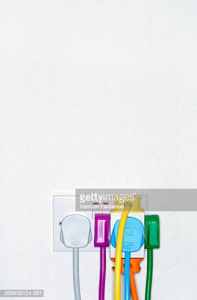 multi-coloured plugs overloading socket, close-up - tomada - fotografias e filmes do acervo