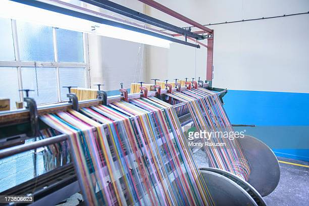 multicoloured threads on industrial loom in textile mill - loom stock pictures, royalty-free photos & images
