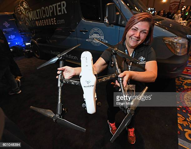 Multicopter Warehouse Vice President of Sales and Marketing Christina Gilson displays a DJI Inspire 1 quadcopter drone at InterDrone an international...