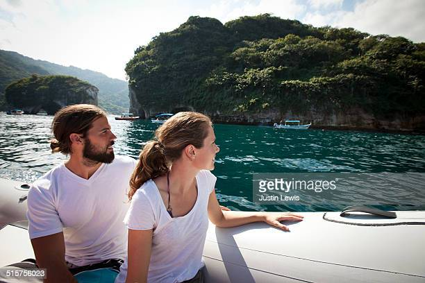 Multicultural Couple Inflatable Boat In Bay