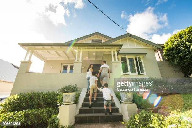 multi-cultural family in australia enters and exits their house - arrival stock pictures, royalty-free photos & images