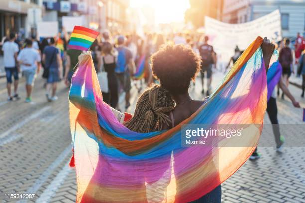 multicultural female couple walking with the pride festival in sofia - pride stock pictures, royalty-free photos & images