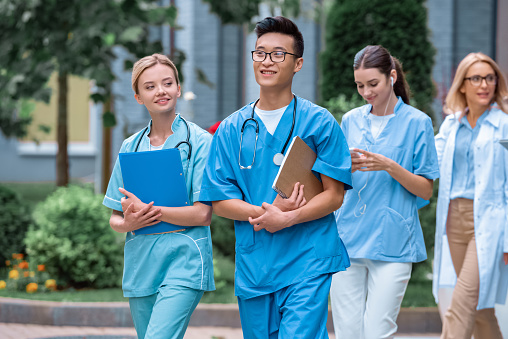 multicultural students and teacher walking on street near medical university 1010601644