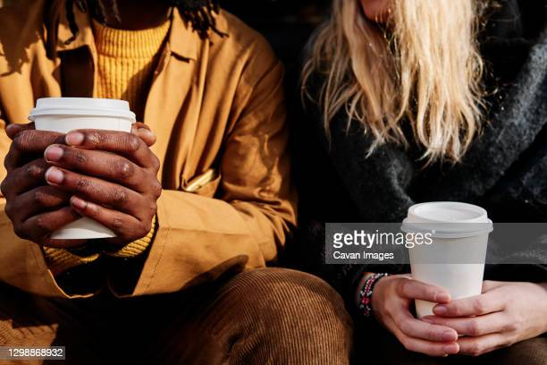 multicultural unrecognizable friends holding a paper cup of coffee while sitting together. focus on the hands. - friendship stock pictures, royalty-free photos & images