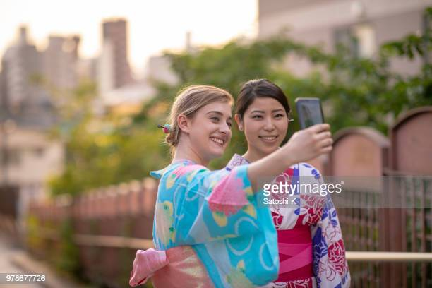 multi-ethinic group of friends in yukata taking picture on slope - turista foto e immagini stock