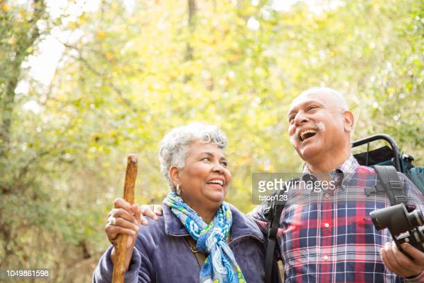 Multi-ethnic, active senior adult couple hiking in wooded forest area.