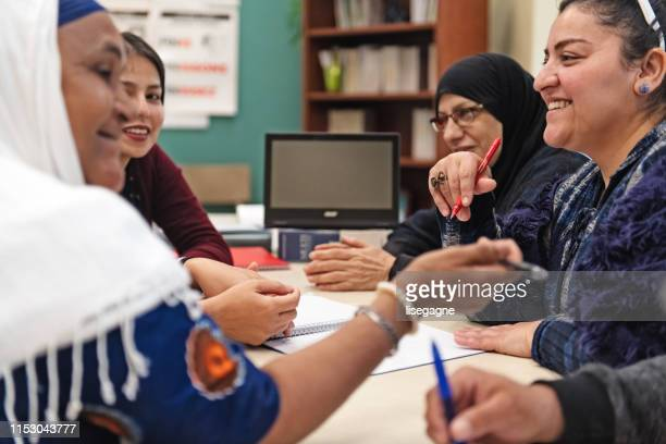 multi-ethnic adults education classroom - settler stock pictures, royalty-free photos & images