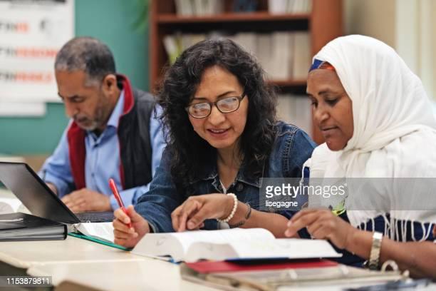 multi-etnische volwassenenonderwijs klaslokaal - emigration and immigration stockfoto's en -beelden