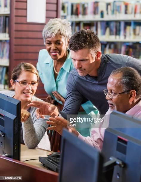multi-etnische volwassenen in de bibliotheek met behulp van computers - gemengde leeftijdscategorie stockfoto's en -beelden