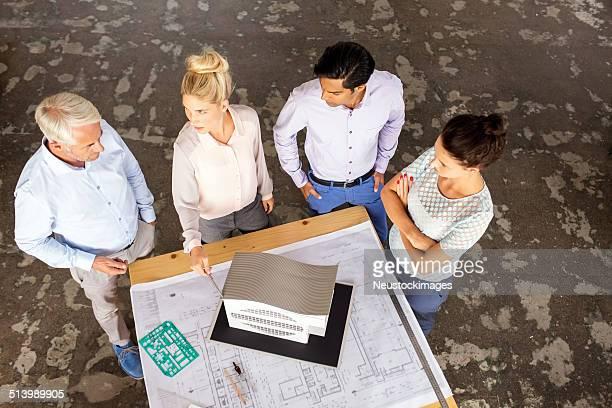 Multi-ethnischen Architekten analysieren Gebäude Modell im Büro-Schreibtisch