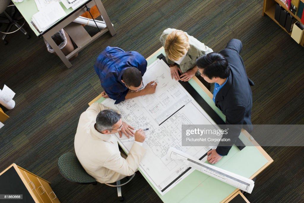 Multi-ethnic architects looking at blueprints : Stock Photo