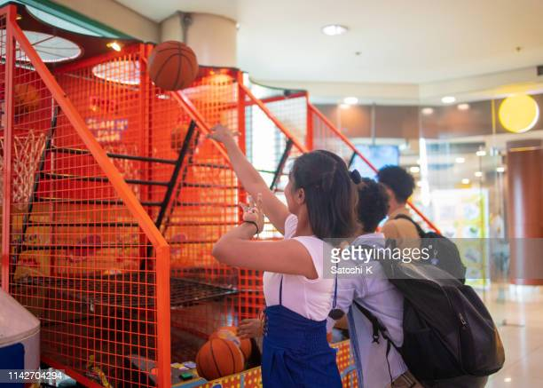 multi-ethnic asian friends playing basket ball in amusement arcade - arcade stock photos and pictures