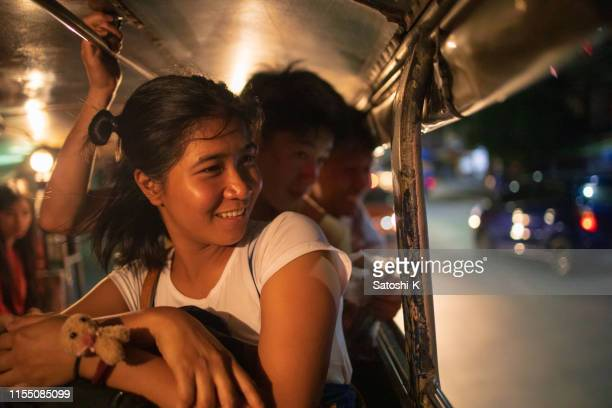 multi-ethnic asian friends riding jeepney in manila at night - manila philippines stock pictures, royalty-free photos & images